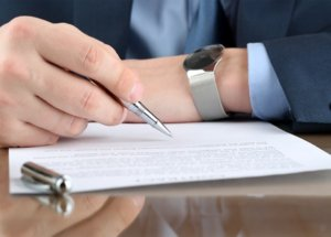 Man holding Pen Reading a Legal Document