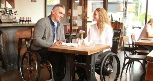 A man and women in wheelchairs at a coffee table