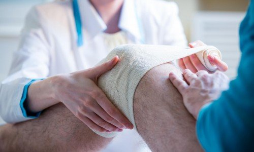 doctor taping up knee